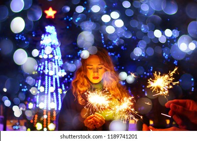 Woman holding sparkler in her hand, celebrating New Year's Eve