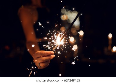Woman holding a sparkler in her hands.