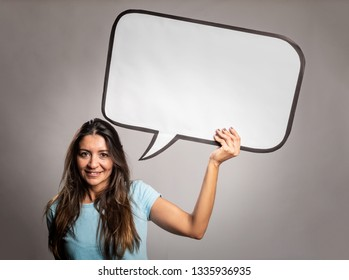 woman holding  a speech bubble on a gray background