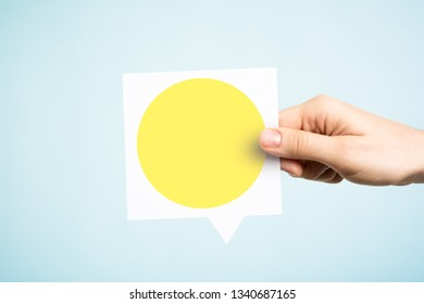 Woman holding a speech bubble with a yellow circle on blue background. Concept of yellow traffic light.