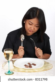 woman holding spoon and fork with chocolates and wine