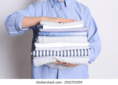 Woman holding stack of clean bed linens on white background, closeup