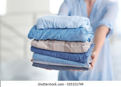 Woman holding stack of clothes, closeup