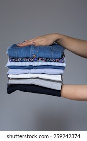 Woman holding stack of clothes in her hands at home