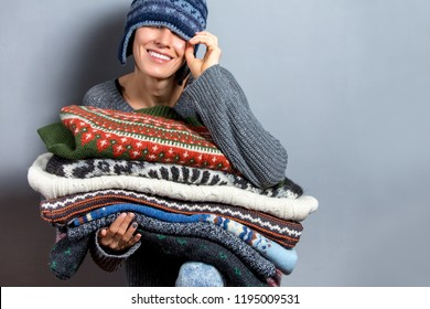Woman holding stack of folded clothes, knitted sweaters and colorful pullovers over grey background