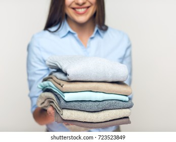 Woman holding stack of folded clothes. Isolated laundry concept.