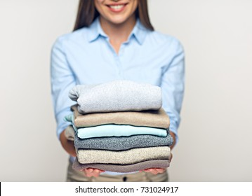 Woman holding stack of folded sweaters. Isolated concept without face.