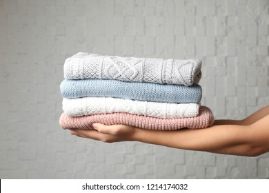 Woman holding stack of folded warm knitted sweaters against brick wall