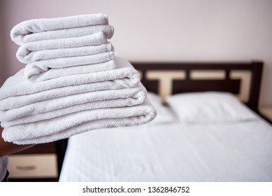 Woman holding stack of fresh white bath clean towels in bedroom interior, copy space. Close up hands of hotel maid with towels. Room service