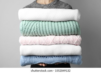 Woman holding stack of warm clothes on grey background, closeup. Autumn season