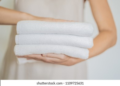A woman is holding a stack of white towels. Concept of service in hotels, laundry, spa.
