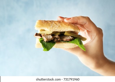 Woman holding steak sandwich on light background