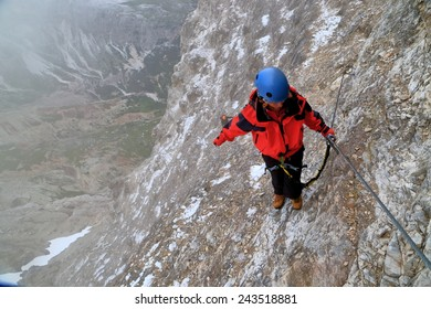 "Woman holding to the steel cable on via ferrata ""Lipella"", Tofana massif, Dolomite Alps, Italy"
