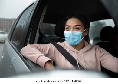 Woman holding steering wheel, driving car, insurance, driving school. Smiling millennial african american woman with seat belt, in protective mask stops and looks through open window, copy space