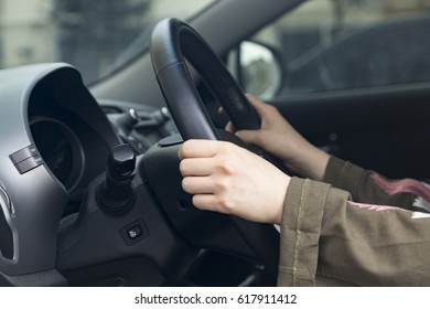 a woman is holding the steering wheel on the car