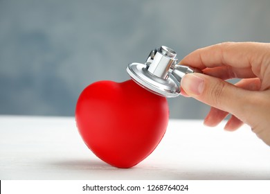 Woman holding stethoscope near red heart on wooden table, closeup. Cardiology concept