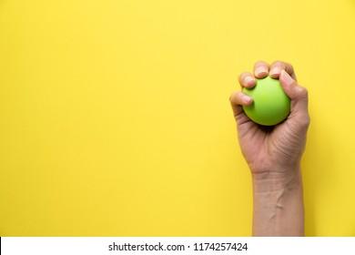 woman holding stress ball on yellow background
