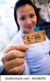 Woman holding subway ticket to Harajuku station in Tokyo, Japan