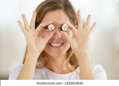 woman holding a suchi roll in front of each eye