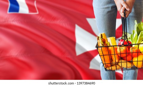 Woman is holding supermarket basket, Wallis And Futuna waving flag background. Economy concept for fresh fruits and vegetables.