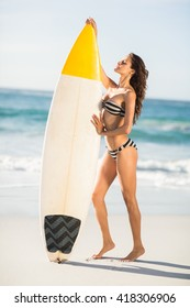 Woman holding surfboard at the beach on a sunny day