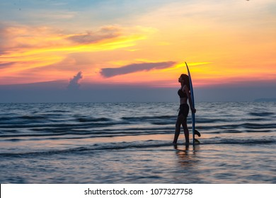 woman holding a surfboard in hand laying on back beside, on returning home station after played surf in the sea at sunset