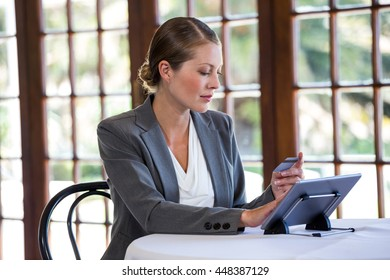 Woman holding tablet and credit card in a restaurant