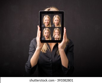 Woman holding tablet with different faces in front of her