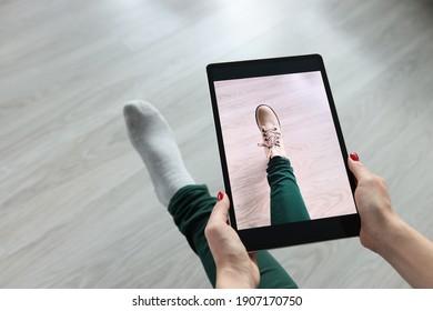 Frauen, die eine Tablette über ihrem Bein halten und Schuhe anprobieren, Nahaufnahme. Konzept des Online-Umkleideraums