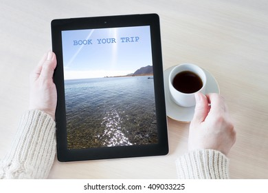 Woman holding tablet pc with sea view wallpaper, booking a trip, at the desk with a cup of coffee