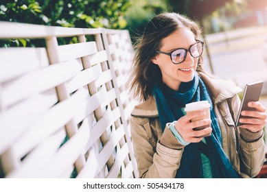 Woman holding takeaway coffee and using smart phone outdoor