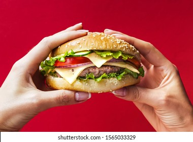 Woman holding tasty burger in hands and copy space, Breakfast concept, Shopkeeper's market photo, Delicious food concept, Fast food concept, Food and drink.