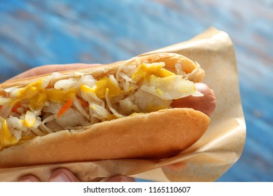 Woman holding tasty hot dog with sauerkraut on color background, closeup