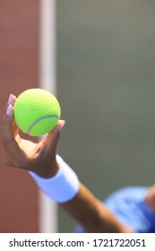 Woman holding a tennis ball with tennis court in the background.