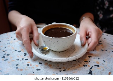 Woman holding a terrazzo cup of coffee in a cafe
