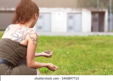 woman is holding and throwing seed balls or seed bombs in front of a ugly grey building, concept guerilla gardening