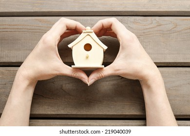 Woman holding tiny wooden house