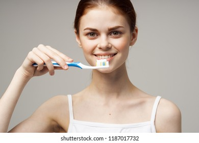 a woman is holding a toothbrush with a tooth paste next to her face