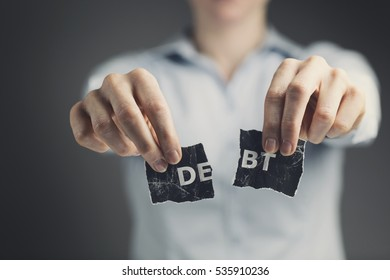 Woman holding a torn label with the word debt toward the camera.