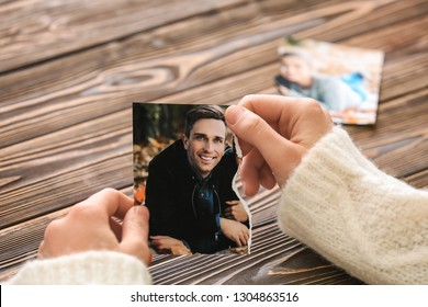 Woman holding torn part of photo with her ex-husband. Concept of divorce