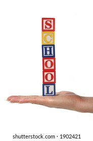 A woman holding toy blocks spelling school