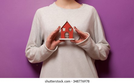 Woman holding a toy house on violet background