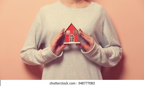 Woman holding a toy house on pink background