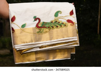Woman holding Traditional handmade white silk sari/ saree with golden details, woman wear on Onam festival, Vishu, wedding, in Kerala India. Close up of traditional Kerala Sari with peacock embroidery