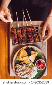 Woman is holding traditional indonesian grilled skewers of tempe. Mexican nachos and guacamole aside with main dish. Vegan food concept.