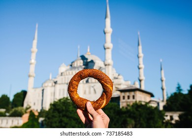 A woman is holding a traditional Turkish bagel named Simit in the background of the Blue Mosque in Istanbul, Turkey. Traditions, tourism, recreation