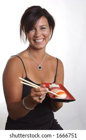 A woman holding a tray of sushi, and smiling.