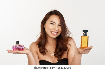 woman holding two bottle of perfume