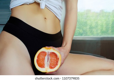 A woman is holding Two fingers on grapefruit by her panties. Concept masturbation