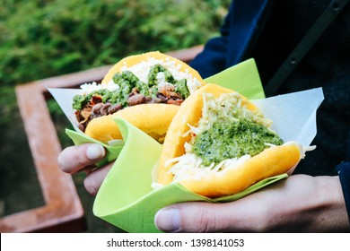 Woman holding two fried Arepas, a typical Venezuelan Street Food with green Salsa, cheese and beans at a Street Food Festival in Dusseldorf, Germany